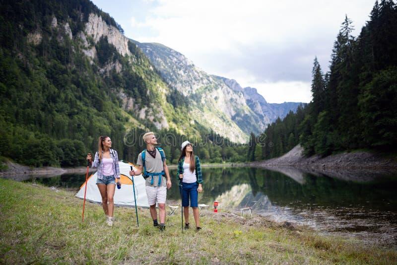 Grupo de amigos jovenes que caminan en campo Gente feliz multirracial que viaja en naturaleza imágenes de archivo libres de regalías