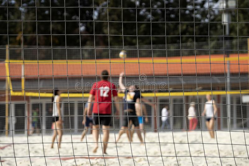 Grupo de amigos jovenes que juegan al voleibol de playa, día de verano, foco del selectiv Fondo borroso, forma de vida sana imágenes de archivo libres de regalías