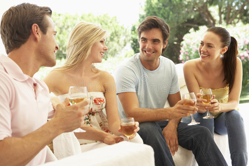 Grupo de amigos jovenes que se relajan en Sofa Drinking Wine Together imagen de archivo