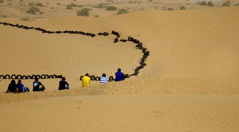Grupo de amigos jovenes que se sientan junto en un desierto en Dubai, UAE imagen de archivo