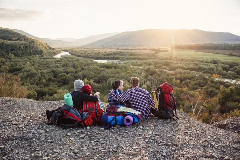 Grupo de amigos jovenes que viajan junto en montañas Viajeros felices del inconformista con las mochilas que se sientan en el top foto de archivo libre de regalías
