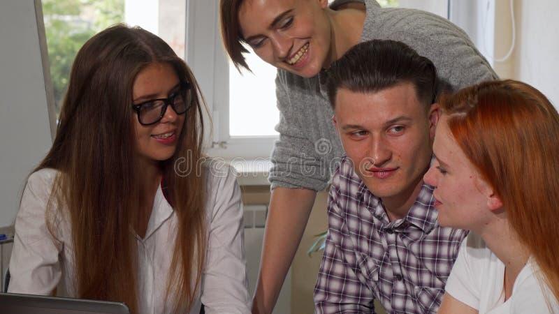 Grupo de amigos de la universidad que hablan, mientras que trabaja en un proyecto junto fotos de archivo libres de regalías