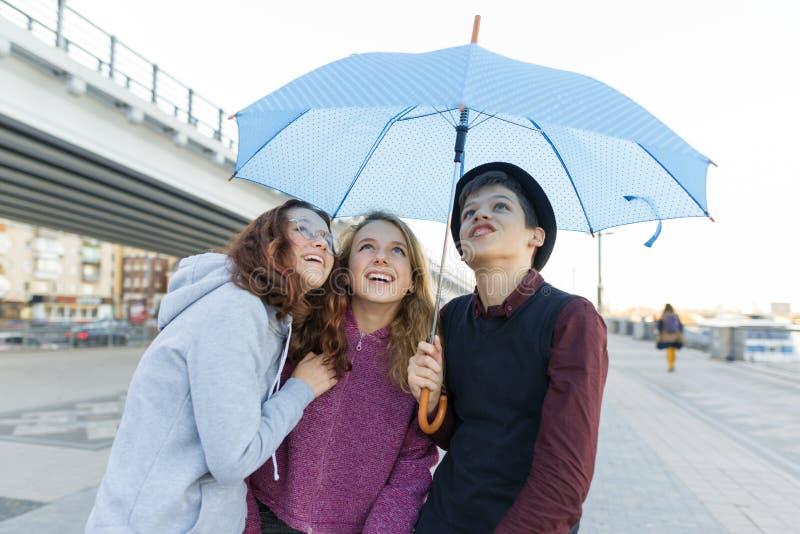 Grupo de amigos de los adolescentes que se divierten en la ciudad, niños de risa con el paraguas Forma de vida adolescente urbana imagen de archivo