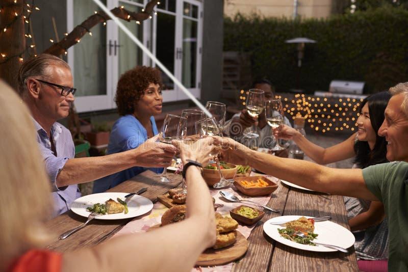Grupo de amigos maduros que apreciam a refeição exterior no quintal fotografia de stock royalty free