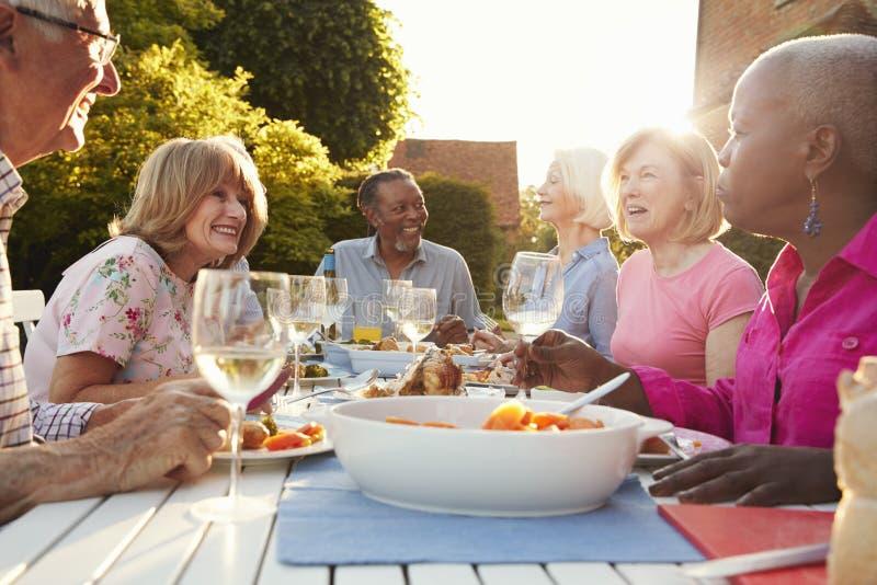 Grupo de amigos mayores que disfrutan del partido de cena al aire libre en casa fotos de archivo