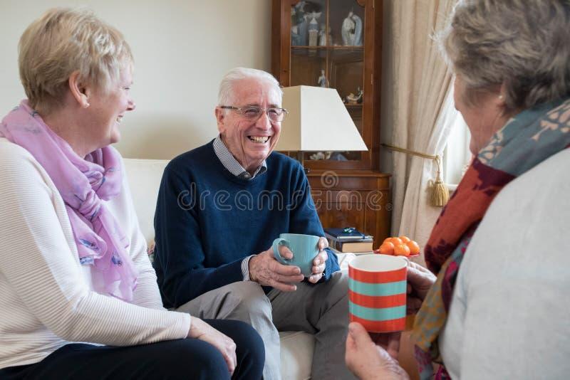 Grupo de amigos mayores que se encuentran en casa para el café fotografía de archivo libre de regalías