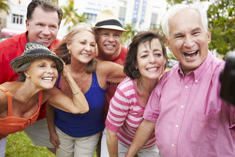 Grupo de amigos mayores que toman Selfie en parque foto de archivo