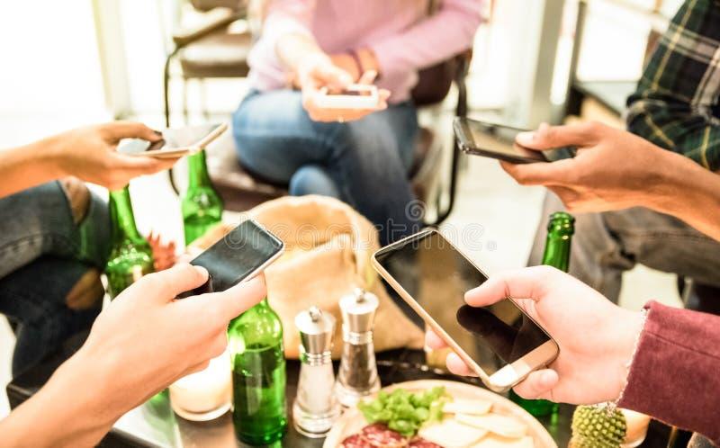 Grupo de amigos multiculturais que têm o divertimento em telefones celulares móveis foto de stock