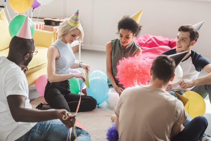 grupo de amigos multiculturales jovenes en los sombreros del partido que se sientan en piso con los globos en adornado imagenes de archivo