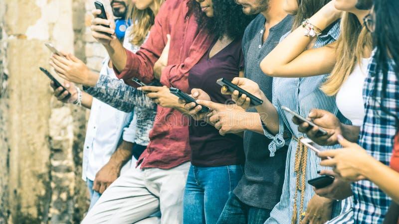 Grupo de amigos multiculturales que usan el teléfono elegante móvil foto de archivo