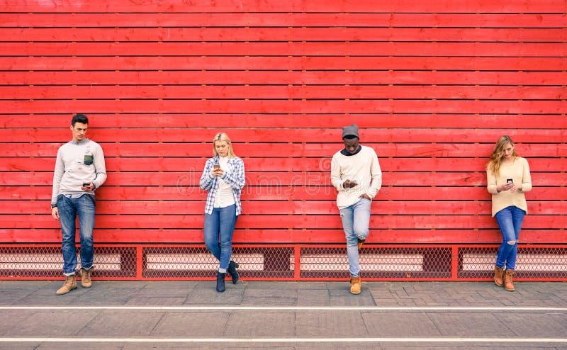Grupo de amigos multirraciais da forma que usam o smartphone imagem de stock