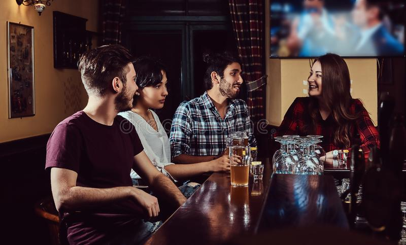 Grupo de amigos multirraciales felices que descansan y que hablan en la barra o el pub imagenes de archivo