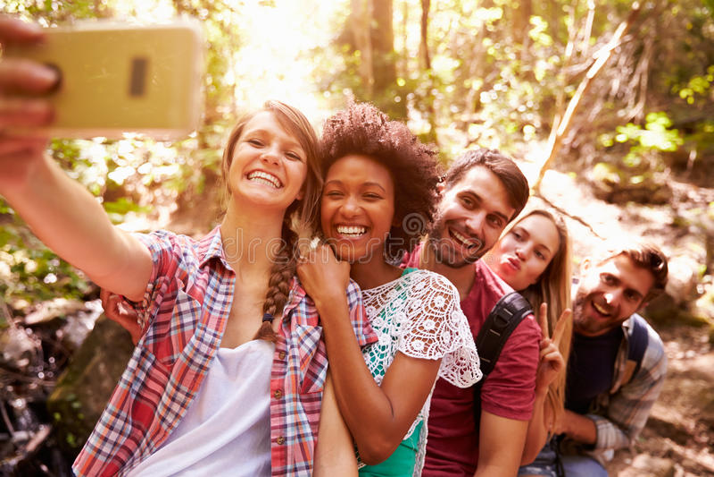 Grupo de amigos na caminhada que toma Selfie na floresta fotos de stock royalty free