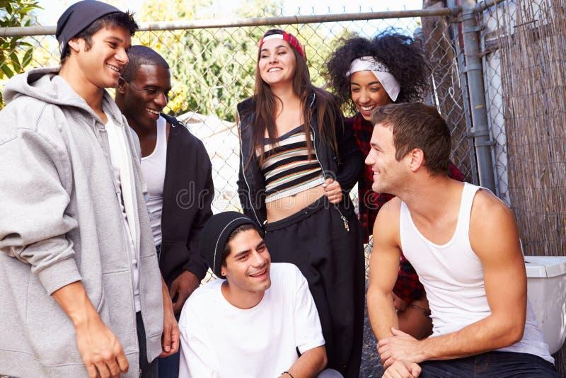 Grupo de amigos no ajuste urbano que está pela cerca fotografia de stock royalty free