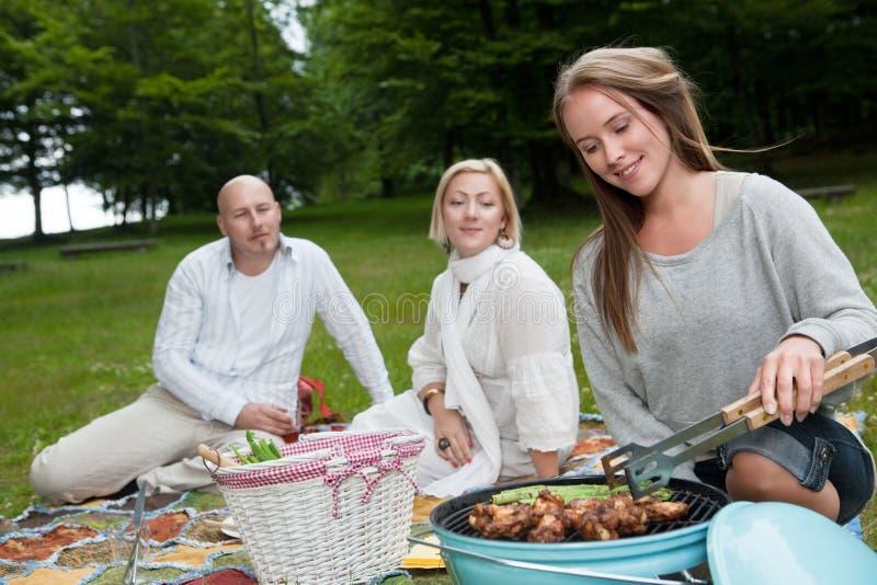 Grupo de amigos no parque com BBQ imagem de stock