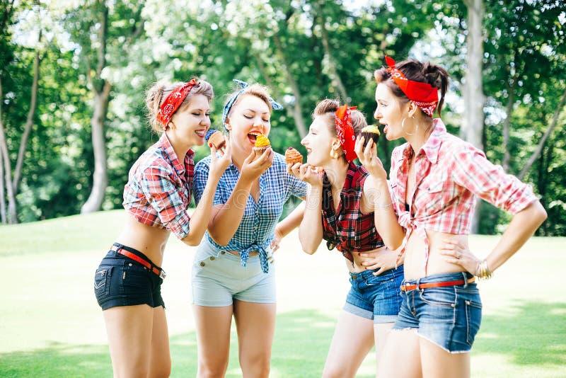 Grupo de amigos no parque que tem o partido do divertimento Meninas alegres com bolos nas mãos Estilo retro foto de stock royalty free