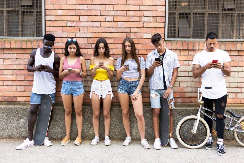Grupo de amigos novos do moderno que usam o telefone esperto em uma área urbana foto de stock royalty free