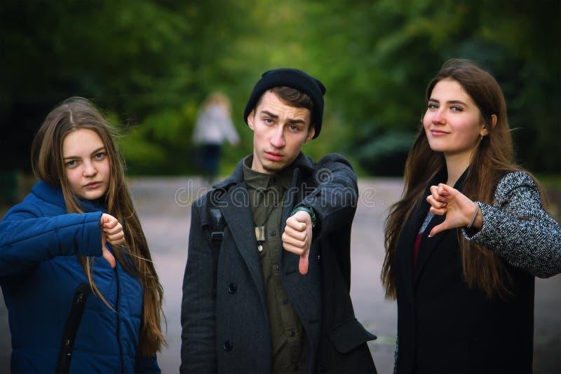 Grupo de amigos novos que mostram o polegar para baixo imagens de stock