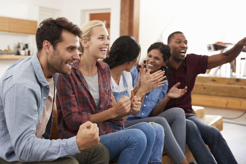 Grupo de amigos novos que olham esportes na televisão e no Cheerin fotografia de stock royalty free