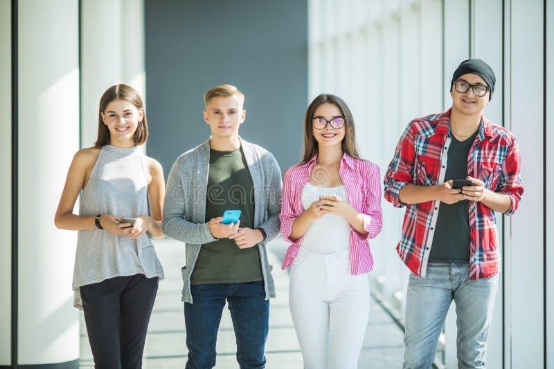 Grupo de amigos novos que olham seus telefones espertos sem interagir-se dentro Conceitos do estilo de vida, tecnologias a imagem de stock royalty free