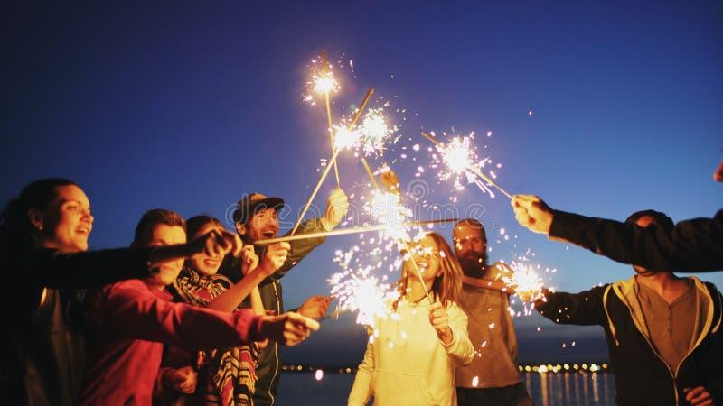 Grupo de amigos novos que têm um partido da praia Amigos que dançam e que comemoram com os chuveirinhos no por do sol crepuscular fotos de stock royalty free
