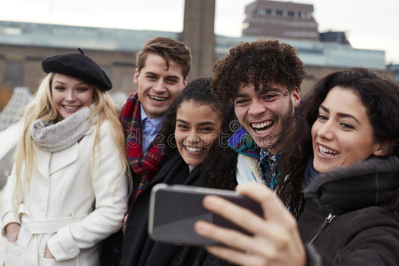 Grupo de amigos novos que tomam Selfie na visita do inverno a Londres imagens de stock