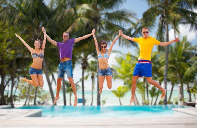 Grupo de amigos o de pares que saltan en la playa fotografía de archivo