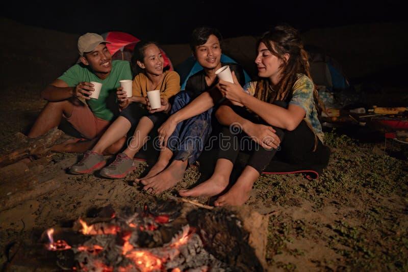 Grupo de amigos que acampam, sentando-se em torno do fogo do acampamento imagem de stock royalty free