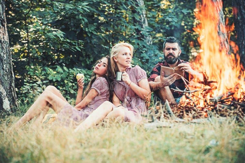 Grupo de amigos que acampan en libro de lectura del individuo del bosque por el fuego Té de consumición de la muchacha rubia herm fotografía de archivo libre de regalías