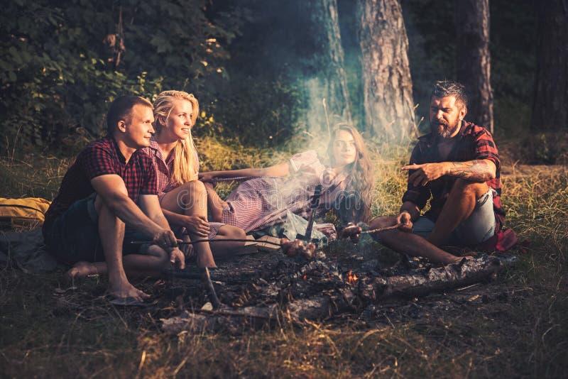 Grupo de amigos que acampan en los pares del bosque dos que fríen las salchichas en los palillos Jóvenes que hablan alrededor de  fotografía de archivo libre de regalías