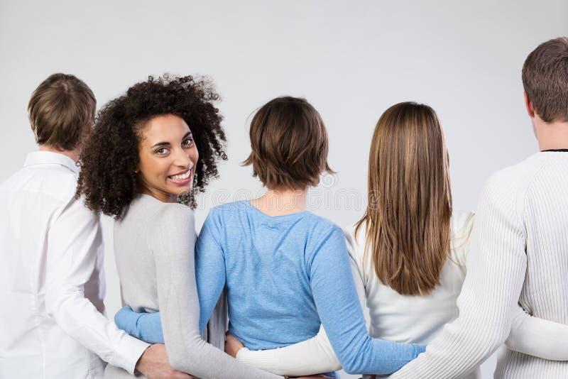 Grupo de amigos que andam afastado braço no braço imagens de stock royalty free