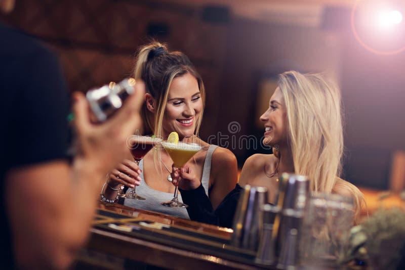 Grupo de amigos que apreciam a bebida na barra foto de stock