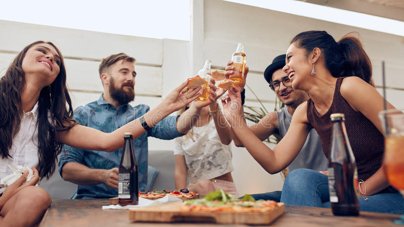 Grupo de amigos que brindam cervejas em um partido fotografia de stock royalty free
