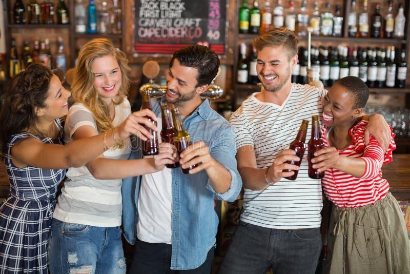 Grupo de amigos que brindam garrafas de cerveja no bar foto de stock