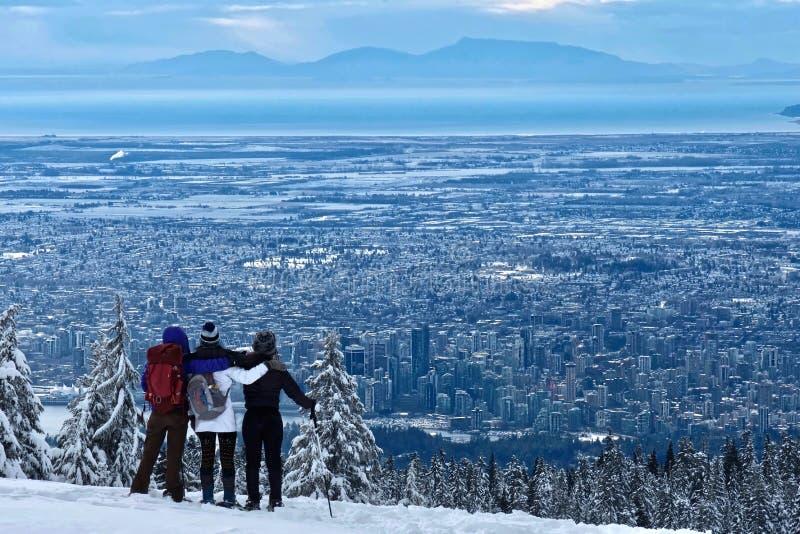 Grupo de amigos que caminan la montaña de Cypress que mira la opinión céntrica de Vancouver en invierno imagen de archivo libre de regalías