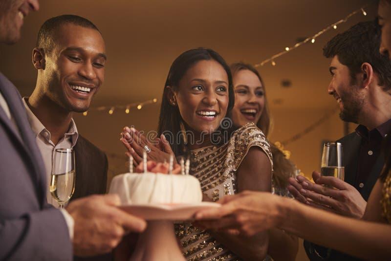 Grupo de amigos que celebran cumpleaños con el partido en casa imagen de archivo