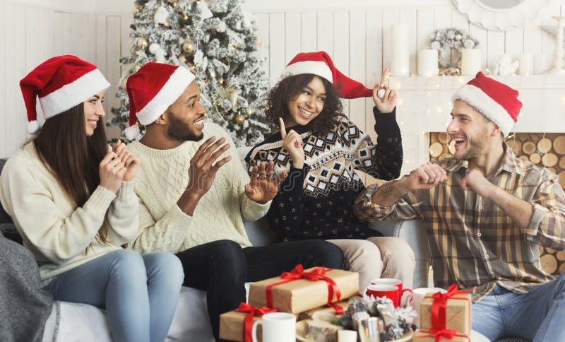 Grupo de amigos que celebran la Navidad en casa imagenes de archivo