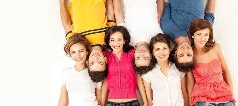 Grupo de amigos que colocam no assoalho, sorrindo foto de stock
