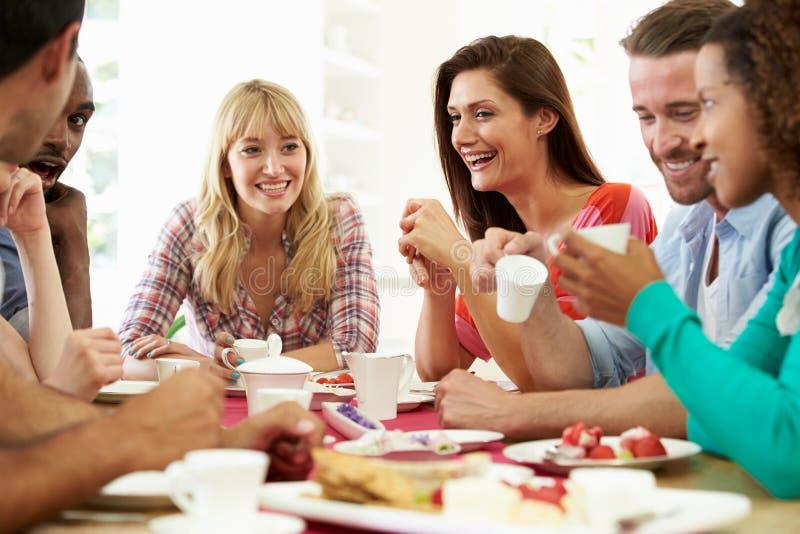 Grupo de amigos que comem o queijo e o café no partido de jantar