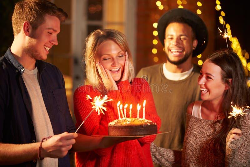 Grupo de amigos que comemoram o aniversário no partido exterior imagem de stock
