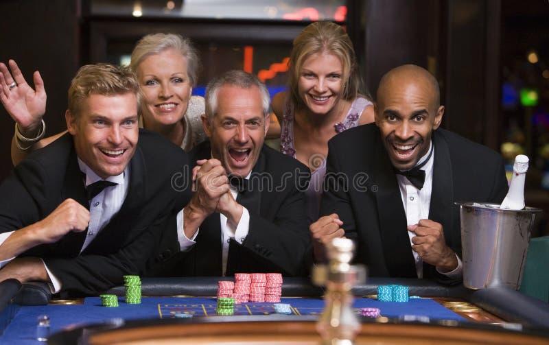 Grupo de amigos que comemoram a vitória na tabela da roleta fotos de stock