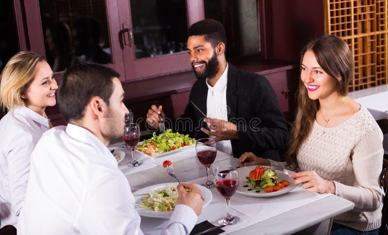 Grupo de amigos que comen en el restaurante fotografía de archivo libre de regalías