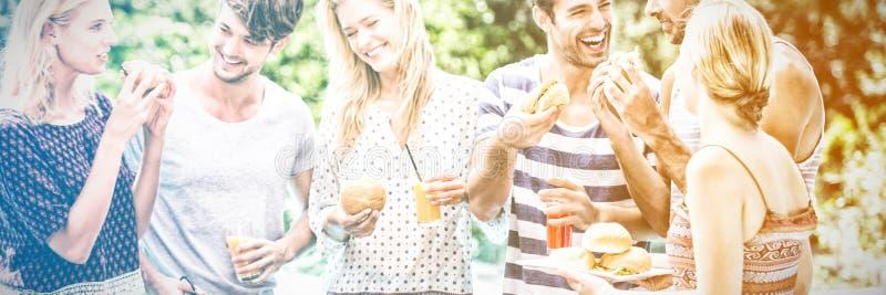 Grupo de amigos que comen hamburguesas y jugo imagen de archivo libre de regalías