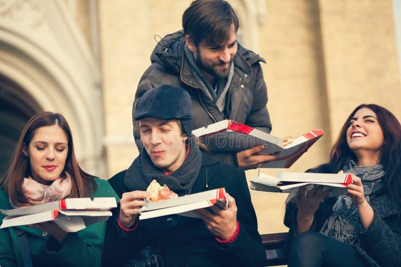 Grupo de amigos que comen la pizza al aire libre foto de archivo libre de regalías