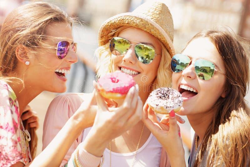 Grupo de amigos que comen los anillos de espuma en la ciudad fotos de archivo libres de regalías