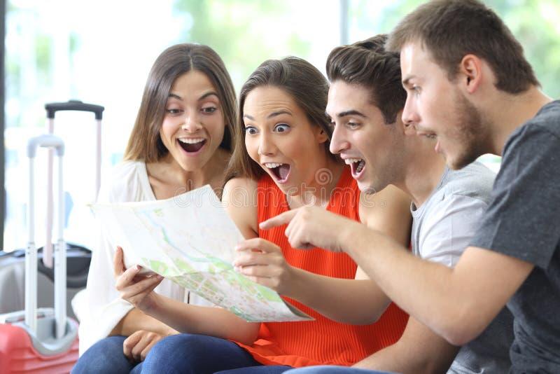 Grupo de amigos que consultan vacaciones del planeamiento del mapa imagen de archivo libre de regalías