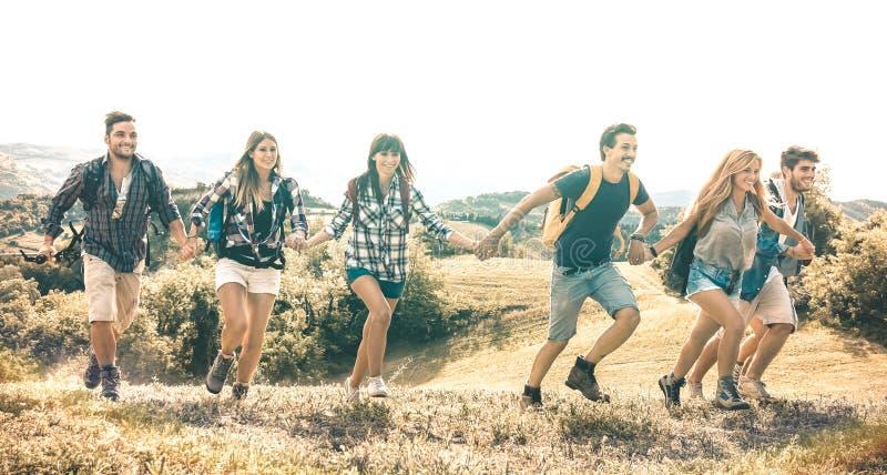 Grupo de amigos que correm no prado da grama no lado do país - amizade e conceito felizes da liberdade com mover-se millenial nov imagem de stock royalty free