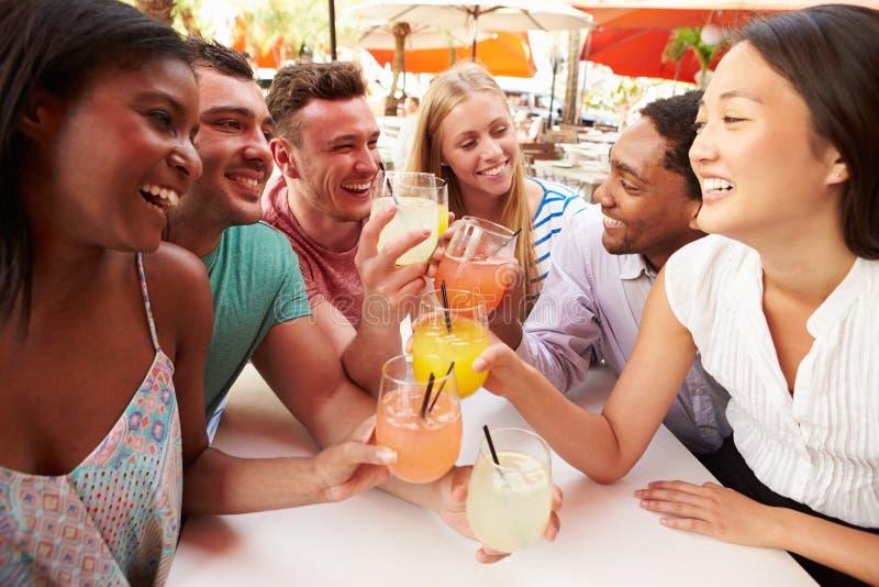 Grupo de amigos que disfrutan de bebidas en restaurante al aire libre fotos de archivo