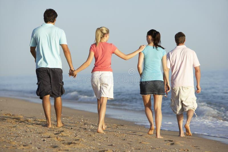 Grupo de amigos que disfrutan de día de fiesta de la playa imagenes de archivo