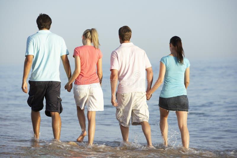 Grupo de amigos que disfrutan de día de fiesta de la playa fotografía de archivo